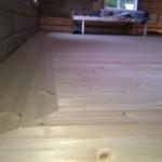 Koko lattiaa kehystää kolmen laudan seinänsuuntainen kehys. Sähkökaapelikouru, hirsien kurkistusluukku tahi hiiri-highway