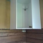Sisäseinän puolen nurkkakaappi on syönyt kytkennät valoille sekä jatkot eteenpäin ulkoseinälle meneville pistorasioille ja valoille. Uudet vanhan ajan pistorasiat näkyvät kaapin alta seinään kiinnitettynä. Kaappien taakse laitettu puukuitulevyä eristeeksi ja ehkäpä hieman seinään oikomaan.